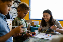 Camp Counselor Teaching Crafts To Boys At Summer Camp