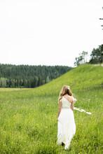 Beautiful Bride In Wedding Dress Walking In Rural Field