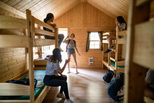 Girl Arriving In Dormitory Cabin At Summer Camp With Friends Waving