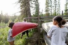 Man And Girls Lifting Canoe Off Rack