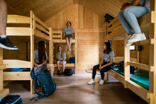 Girls Relaxing In Dormitory Cabin At Summer Camp