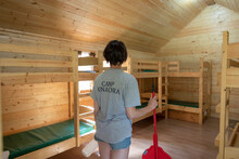 Girl Cleaning Cabin At Summer Camp
