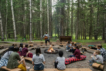 People Listening To Man Playing Guitar By The Campfire