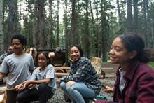 Girls Sitting Around Campfire In Summer Camp