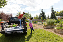 Mother And Son Loading Pickup Truck In Community Garden