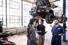 Auto Mechanics Talking Near SUV On Hydraulic Lift In Garage