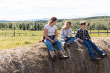 Brother And Sisters In Cowboy Boots On Rolled Hay Bales On Sunny Farm