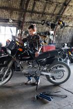 Boy Fixing Motorcycle In Barn Workshop
