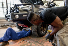 Male Auto Mechanics Working Under Modified SUV In Custom Garage