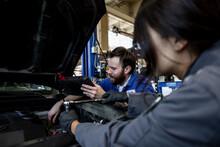 Auto Mechanics Working On Car Engine In Garage