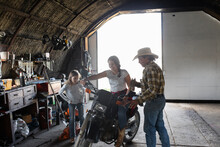Grandfather And Granddaughters In Barn With Motorcycle