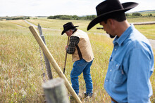 Male Ranchers In Cowboy Hats Fixing Barbed Wire Fence On Sunny Ranch