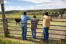 Multigenerational Cattle Ranchers At Sunny Pasture Fence On Ranch