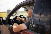 Senior Male Farmer Driving Pickup Truck On Sunny Farm