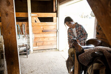 Female Rancher Cleaning Saddle In Horse Barn