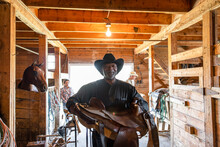 Portrait Confident Senior Male Rancher With Horse Saddle In Barn