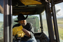 Thoughtful Handsome Senior Male Farmer Driving Tractor