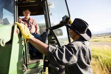Senior Male Farmers Talking At Tractor In Sunny Farm Field