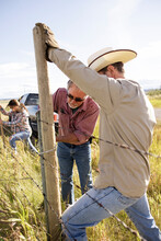 Ranchers Building Fenced With Barbed Wire And Fence Post On Ranch
