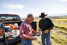 Senior Male Farmers With Tools Outside Pickup Truck In Sunny Field