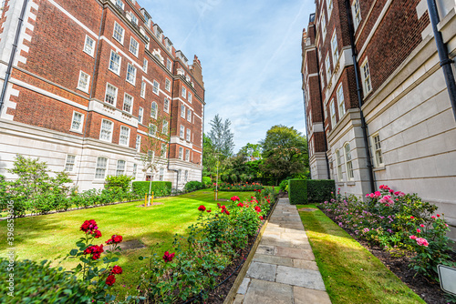 Stampa su Tela London, UK rose garden view with path between white red brick Victorian architec
