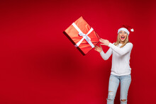Studio Photo Of Excited Blonde Lady In Santa Hat Throwing Gift Box In The Air With Her Mouth Wide Open. Copy Space