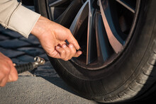 Close Up Of Man Hands Inflating Car Tires. Tire Air Pressure Checking Before Travel.