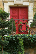 Red Door With Christmas With Wreath Of Christmas Tree Branches And Cones