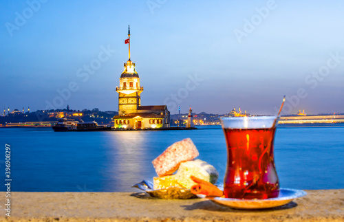 Foto Magnific view of Maiden's Tower (aka Kiz kulesi) at night time on the background and traditional turkish tea with colorful turkish delight on the front
