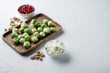 Brussels Sprouts, With Pomegranate, Cottage Cheese And Pistachios, On White Textured Background With Space For Text