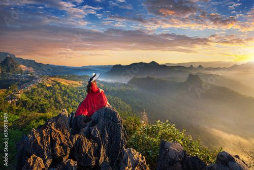Beautiful girl sitting on sunrise viewpoint at Ja Bo village, Mae hong son province, Thailand Fotobehang