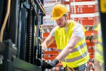 Mechanic Repairing Forklift In Warehouse