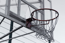 An Old Broken Basketball Basket With Broken Glass And Torn Mesh. Bad Conditions For Sports Concept Photo. Vandalism.