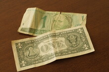 One Brazilian Real And One Dollar Bill On The Table