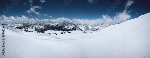 Alpine panorama of the snow-covered Great Caucasus Range on a sunny day with variable cloud cover Canvas Print