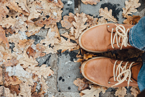 Photo Top view of brown oak leaves, ice and pair of brown leather boots on the floor during winter day