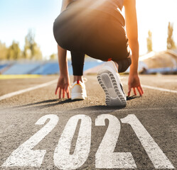 Start new year with fresh vision and ideas. Sporty woman ready for running near 2021 numbers on road, closeup