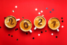 Figures 2021 As A Symbol Of The New Year On Cups Of Hot Aromatic Coffee On A Bright Red Background Among Stars And Marshmallows. Top View, Flat Lay