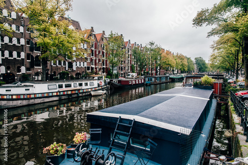 Foto Canal in Amsterdam The Netherlands with several houseboats and water reflection