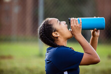 Female Soccer Player Drinking Water On Field