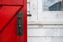 A Vintage Red Exterior Wooden Screen Door On A White Clapboard Wood Building. There's A Closed Clear Glass Window In The Wall. The Door Handle Is An Old Country Cottage Wrought Iron Handle And Latch.
