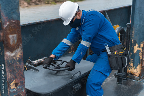 Photo Marine officer opening a hatch on a cargo ship