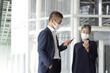スマートフォンを見るマスクをつけたシニア世代ビジネスマンとビジネスウーマン