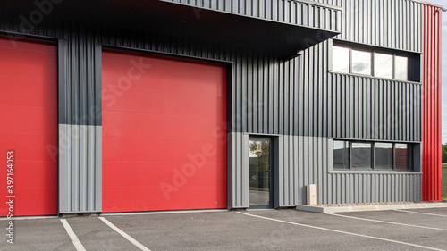 modern industrial unit with two red roller doors