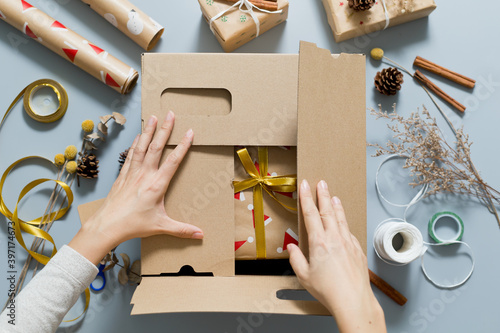 Fototapeta Female packing christmas gifts in shipping box. Concept of Christmas presents delivery parcel. obraz