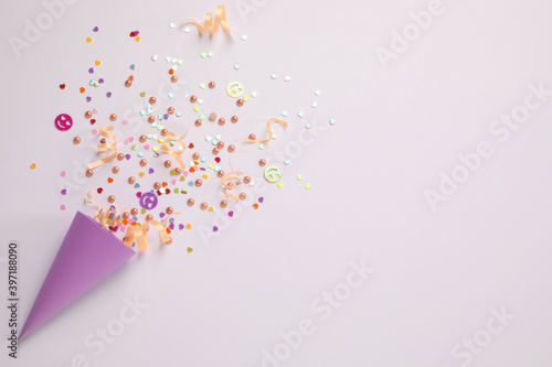 Fényképezés Colorful confetti and streamers with party cracker on white background, top view