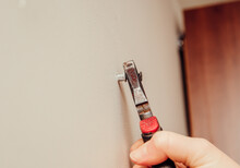 Close Up View Of Person Hand Removing Old Plastic Dowel, Nylon Wall Plug From Drywall With Pliers At Home. Home Renovations Concept.
