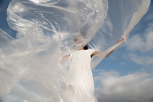 Girl In White Dress Waving With Plastic Sheet In The Sky