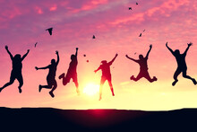 Silhouette Friends Jump And Birds Fly On Sunset Sky At Top Of Mountain Abstract Background.