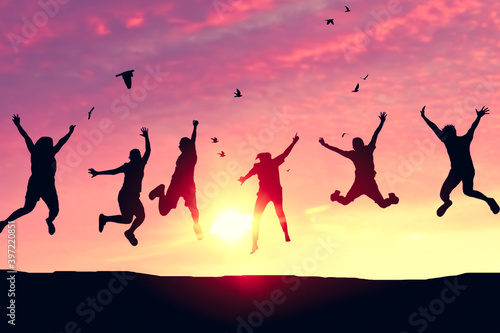 Foto Silhouette friends jump and birds fly on sunset sky at top of mountain abstract background